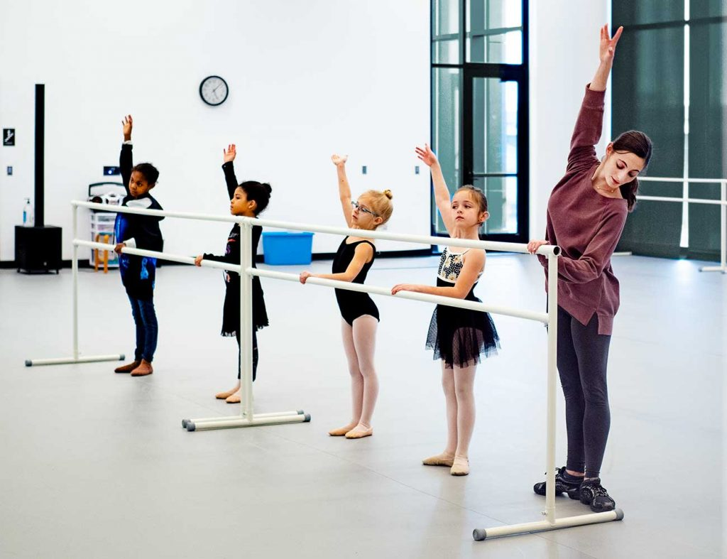 Four young dancers work on posture and positioning at a ballet barre with an American Midwest Ballet instructor.